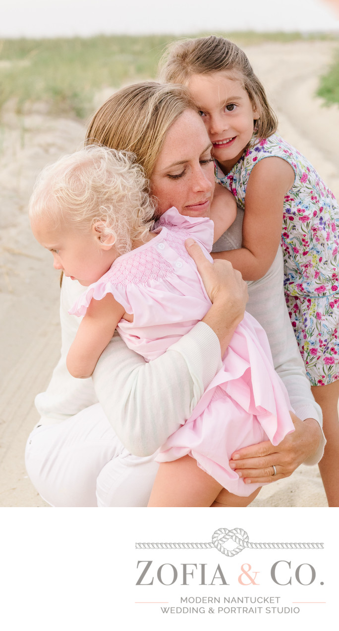 daughters hugging mom on the beach