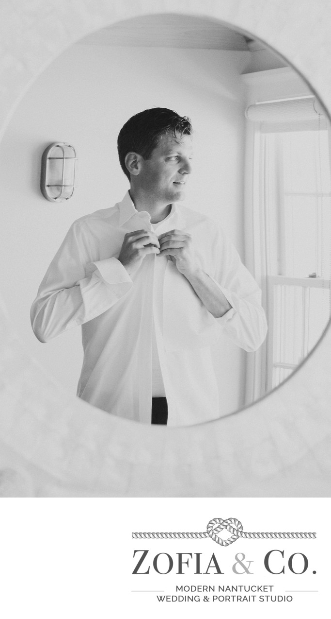 groom in mirror getting ready black and white