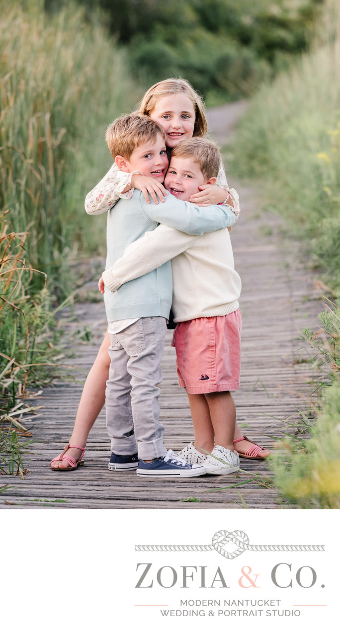 brothers hugging sister at lily pond nantucket