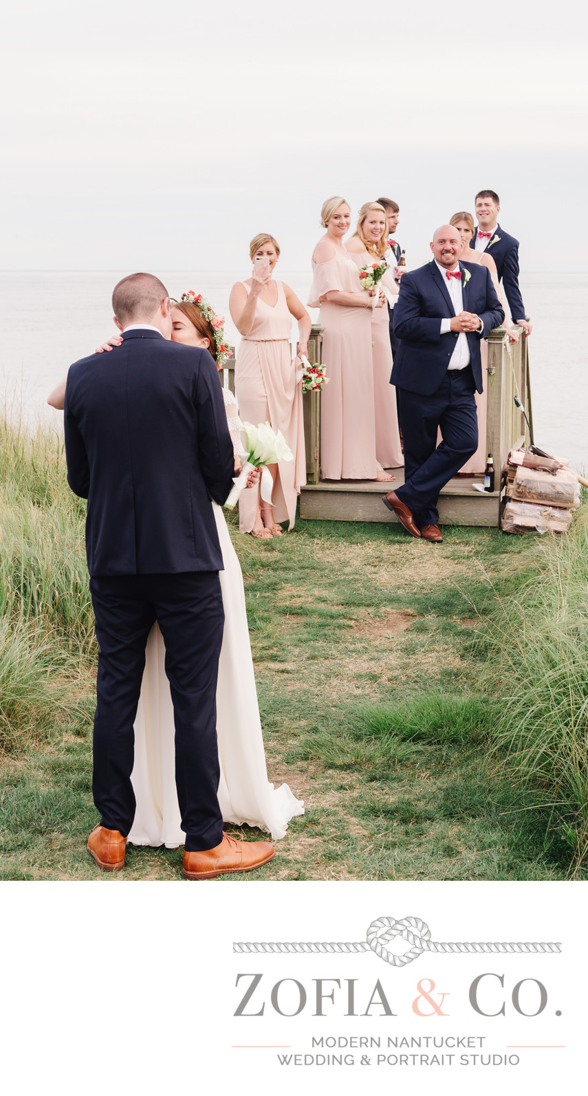 wedding party laughs at nantucket bride and groom kissing in tom nevers