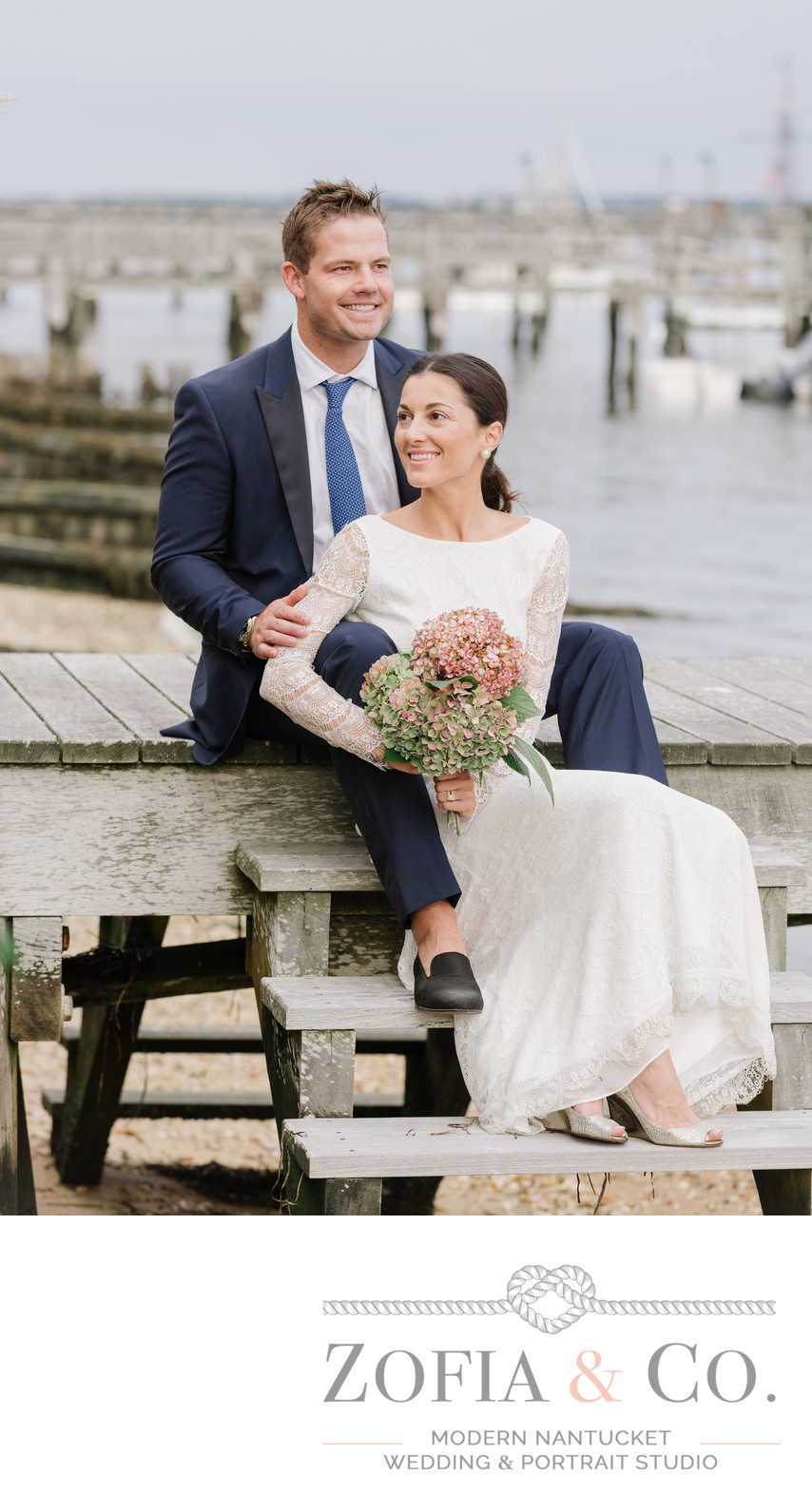 groom in blue suit and bride in lace on nantucket harbor home