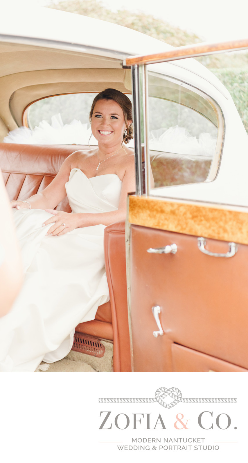 bride in strapless dress in vintage car at st marys church nantucket