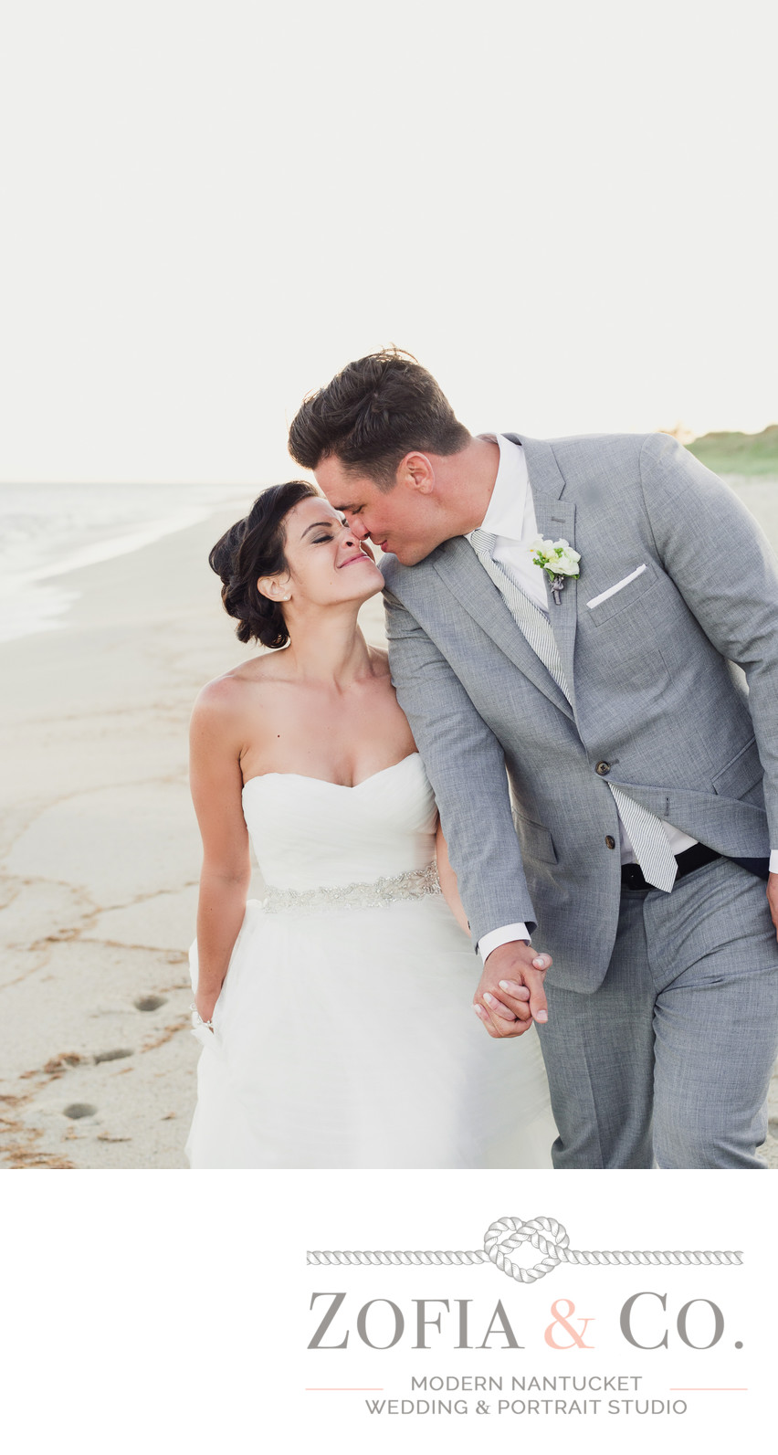 Bride and groom in grey nuzzle on the beach