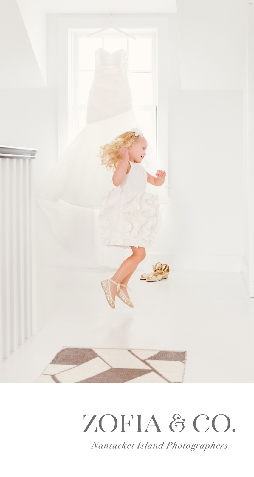 Nantucket Flower Girl jumping in front of bridal gown
