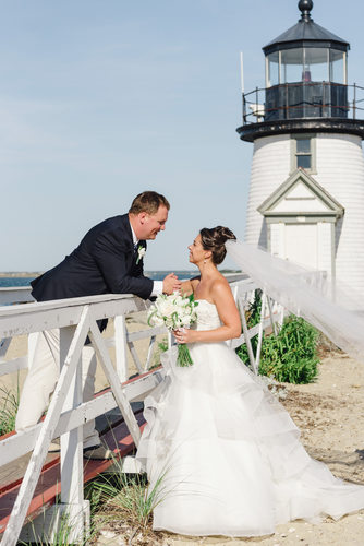 groom smiles at nantucket bride brant point lighthouse