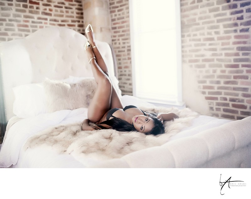 Black woman in white sheets boudoir posing