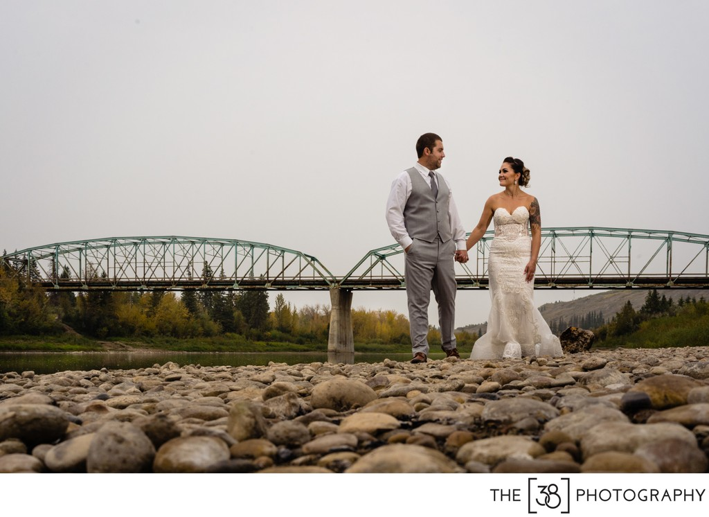 Bride and groom walk along the river