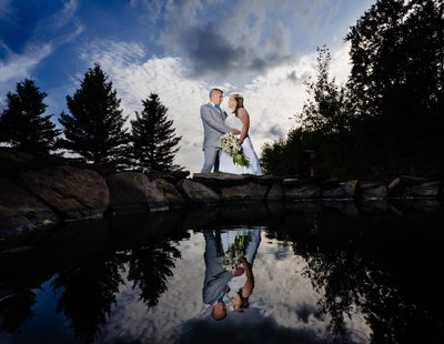 A Photo of a Bride and Groom Near the Pond