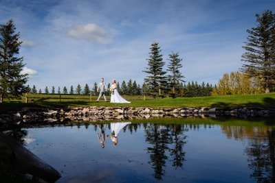 Bride and Groom Walking near the Pond