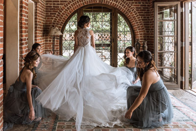 Bridesmaids fixing brides gown
