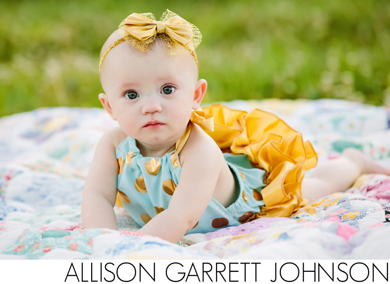 Outdoor baby portrait on vintage quilt
