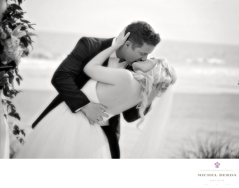 The wedding kiss at wedding ceremony at Sea Side Point Wild Dunes Resort