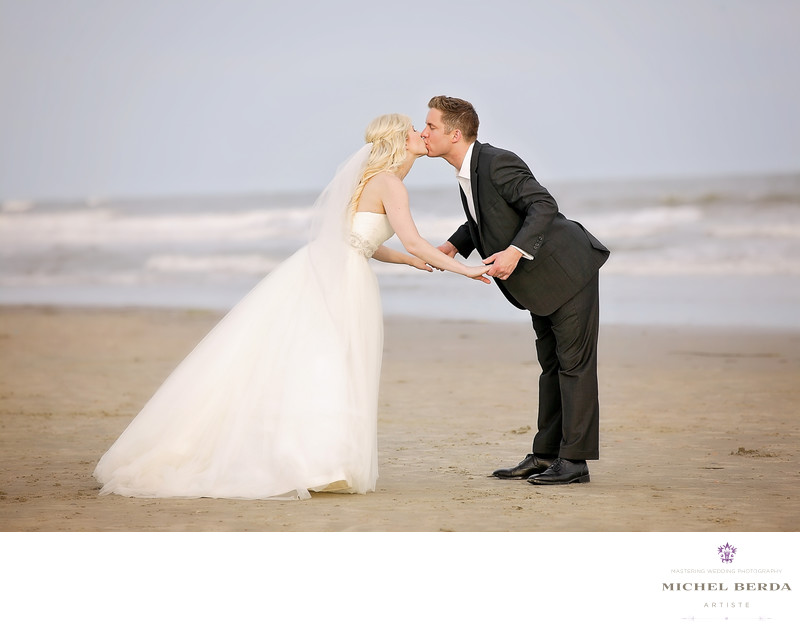 Bride and groom kiss on the beach wedding ceremony at Sea Side Point Wild Dunes Resort