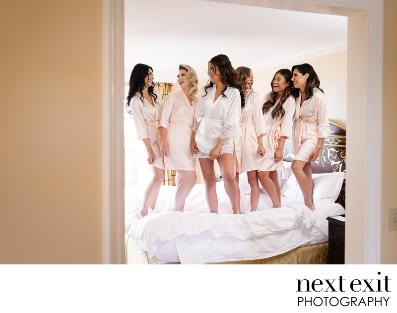 Bridesmaids jumping on the bed at the Langham