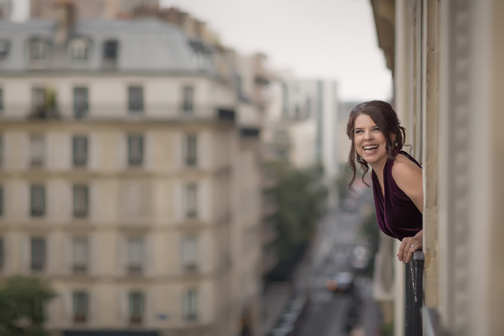Portrait of Woman leaning out a window of Paris Flat