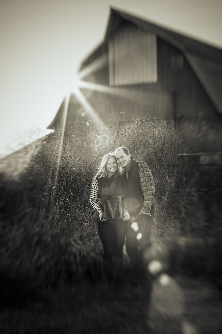 Engagement portrait in sun Flare over a barn