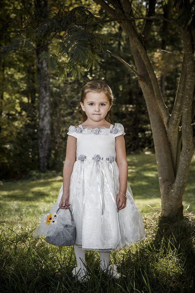 Flower girl of the wedding party with basket of flowers