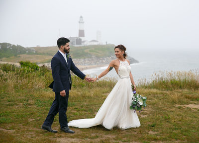 Bride and groom walking at  Camp Hero Montauk Lighthouse. 360 East Montauk Downs