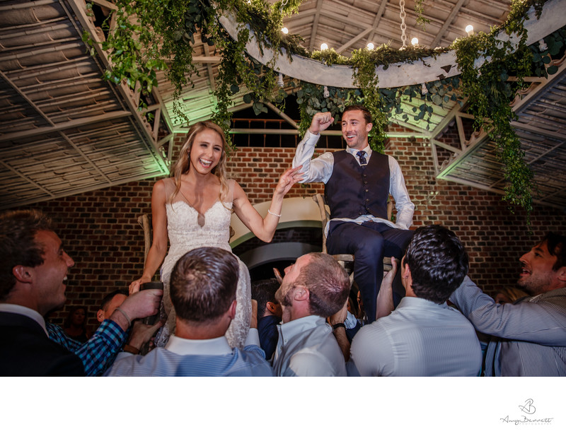 Bride and Groom Carried on Chairs through Reception