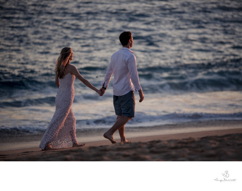 Bride and Groom Walk Down the Beach Holding Hands