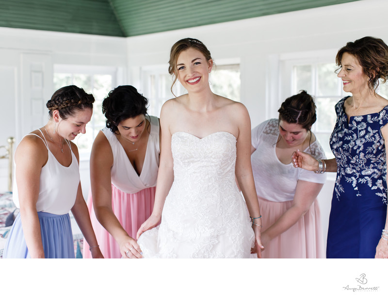 Fussing Bridesmaids with Smiling Bride