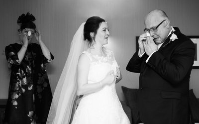 Bride's mother and father getting emotional when seeing their beautiful daughter ready for her wedding.