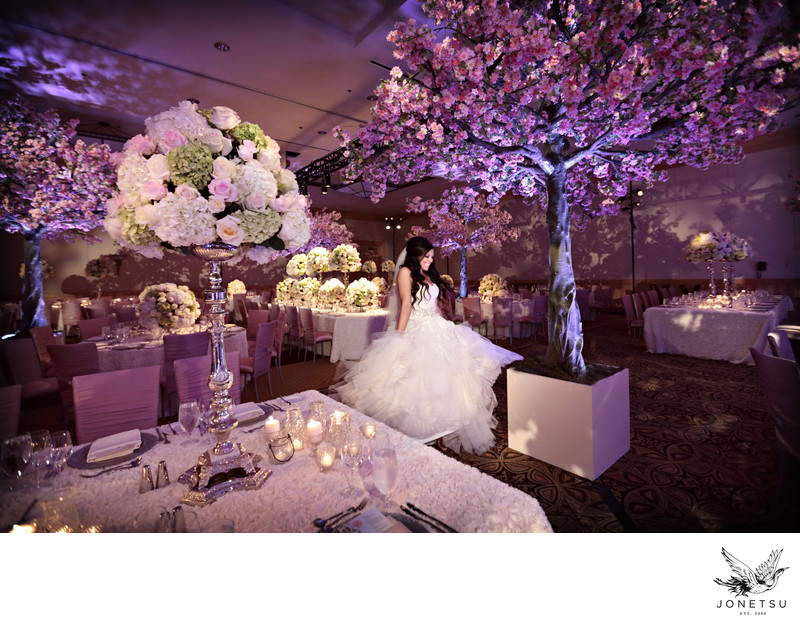 Bride dances under cherry blossom themed wedding decor