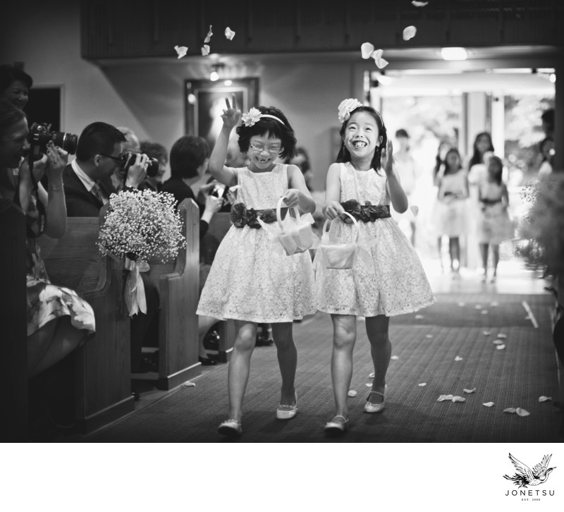 Flower girls enjoy throwing petals at church wedding