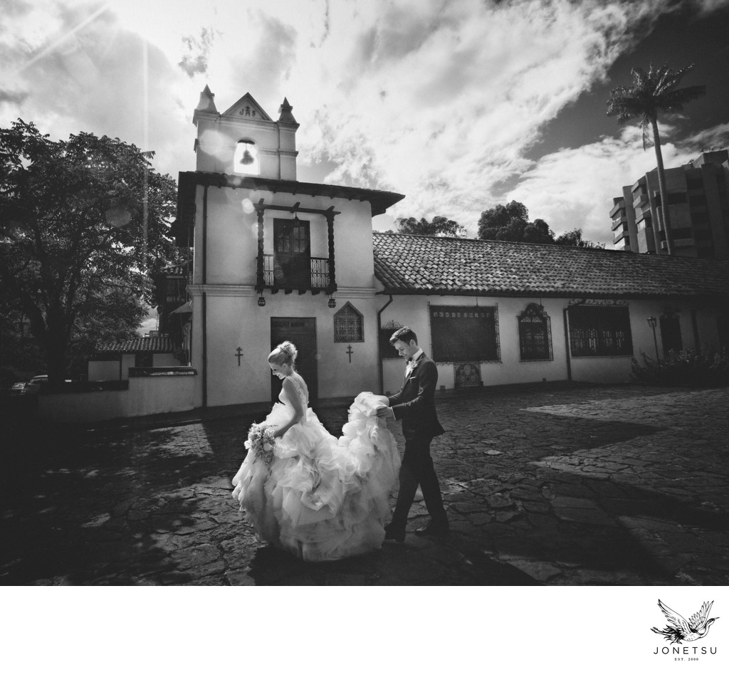 Bride in Lazaro gown in front of church in Bogota