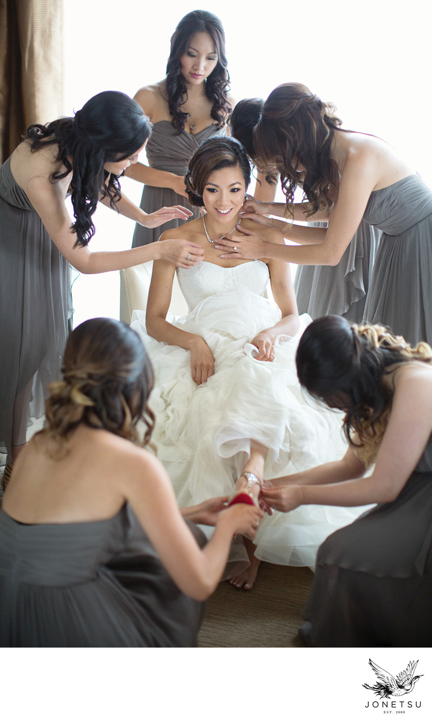Vancouver bridesmaids in gowns help bride in Vera Wang