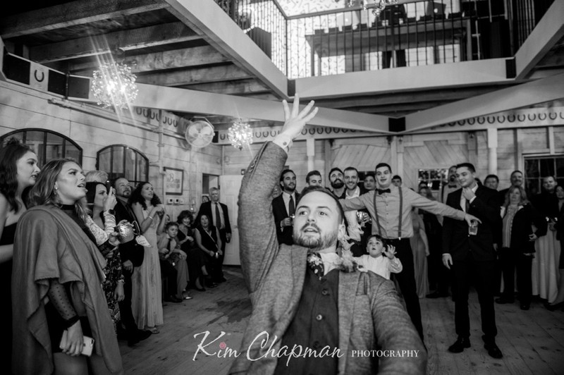Groom Throwing Garter at Barn Weddings