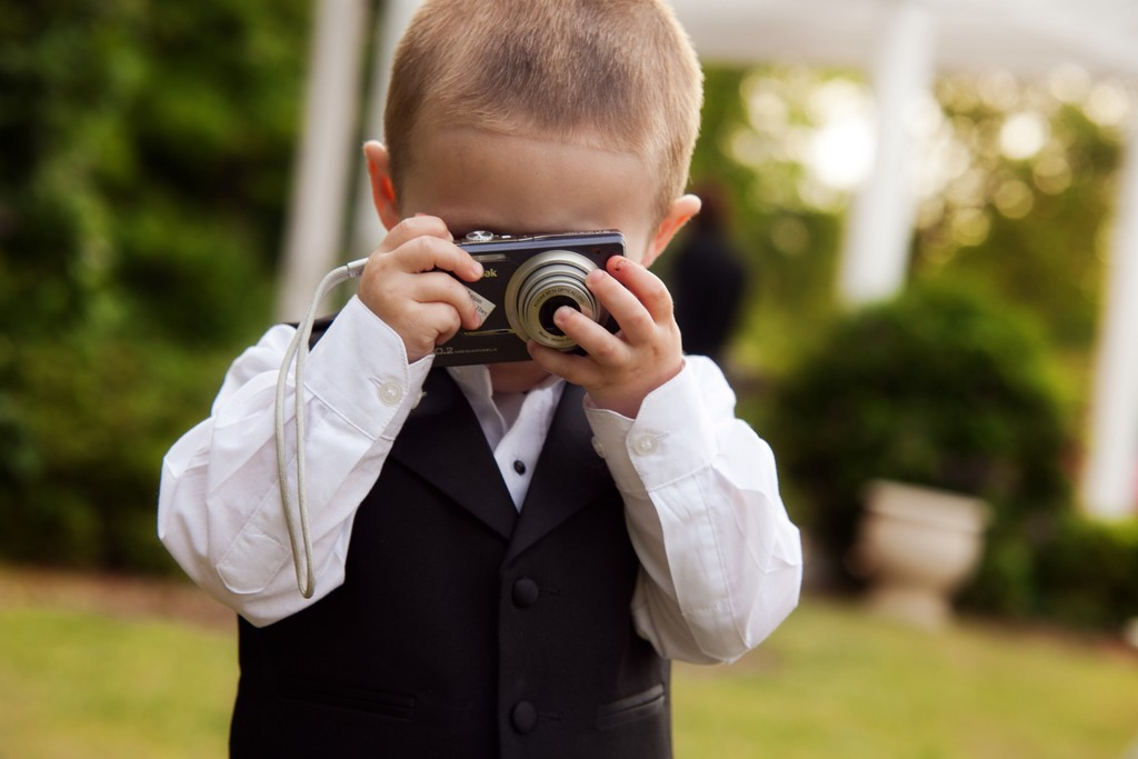 Funny wedding photo of little boy with a camera