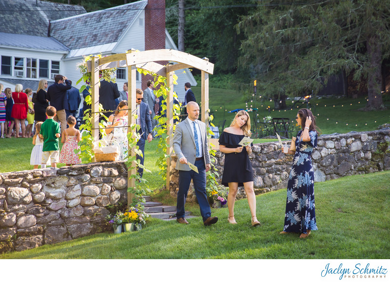 Wedding guests walk through arbor to ceremony