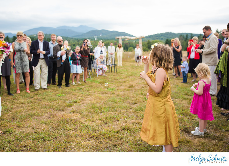 Little girl blowing bubbles VT wedding ceremony