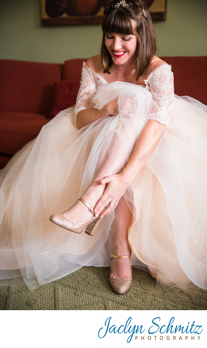 bride laughs when she puts on wedding heels