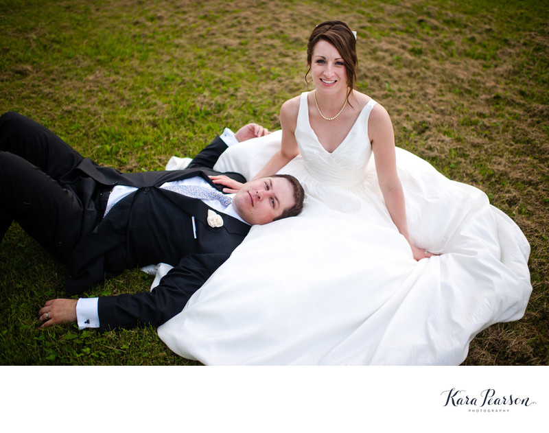Bride And Groom Laying In Grass