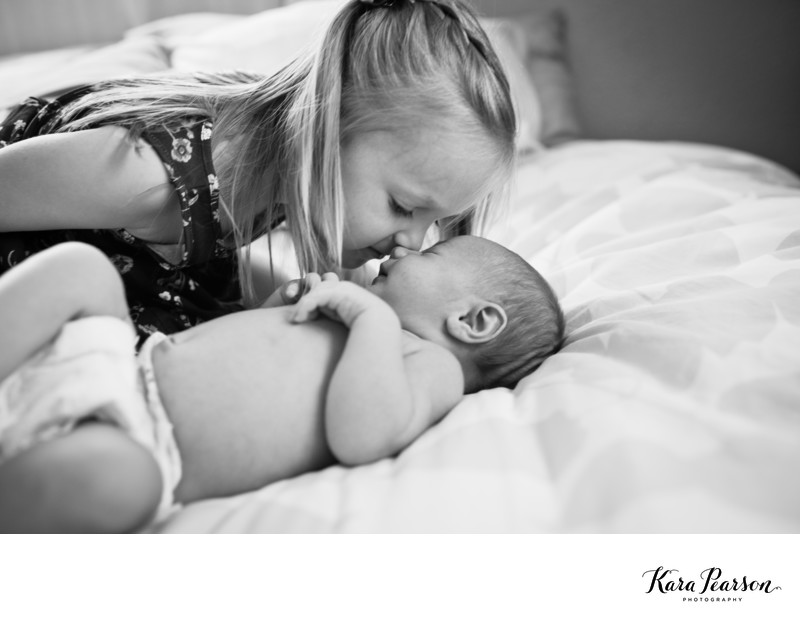 Sisters Kiss During Newborn Portraits