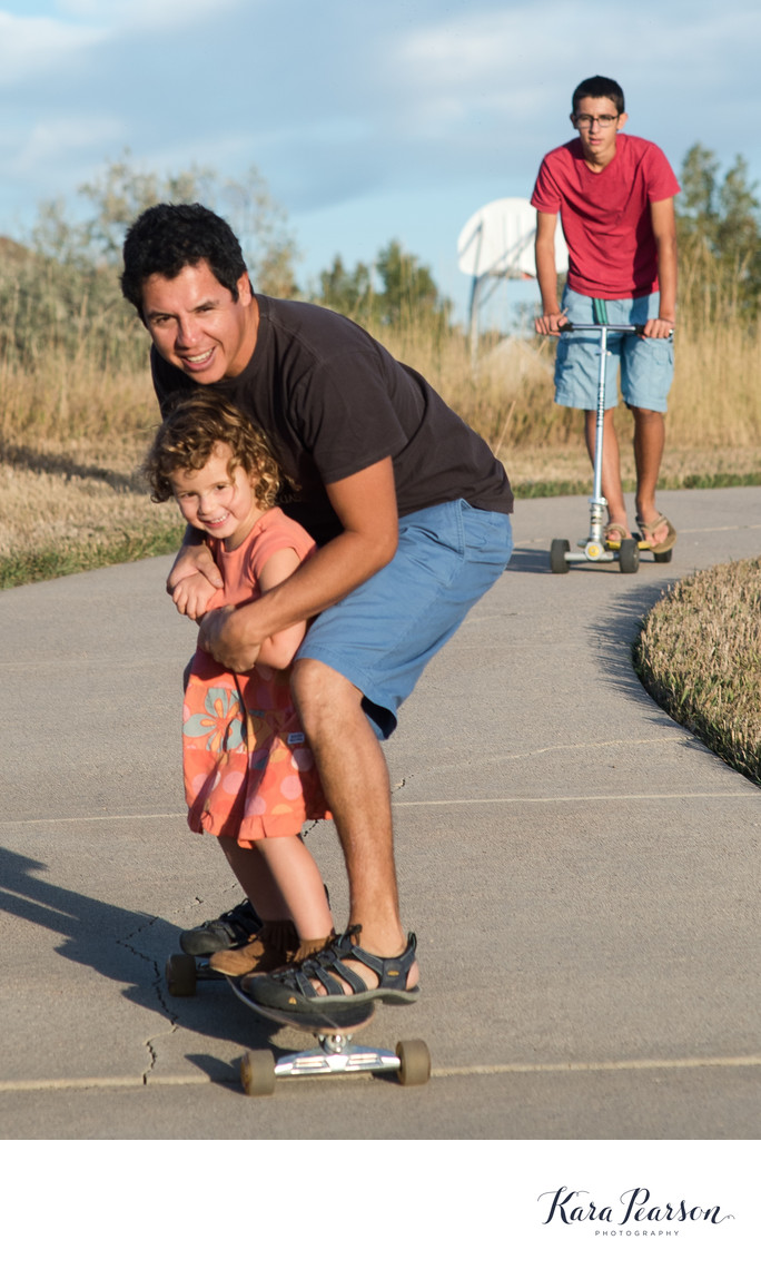Girl On Skateboard With Her Dad