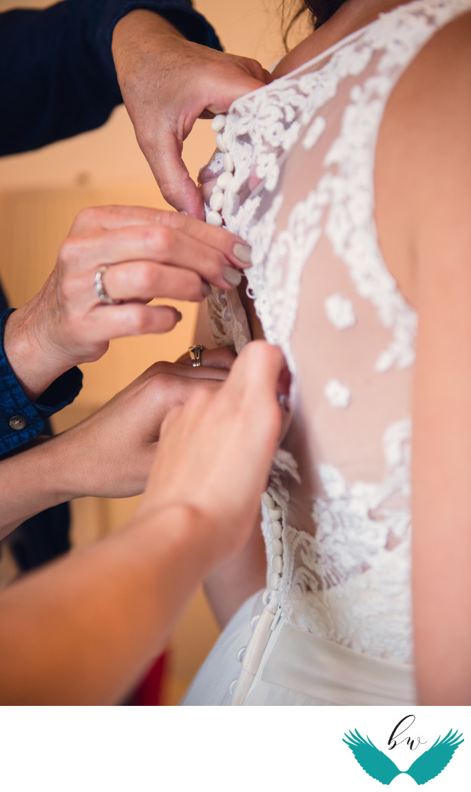 Many hands buttoning the wedding dress
