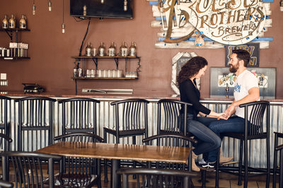 Boese Brothers engagement session: Lexi + George sitting at bar
