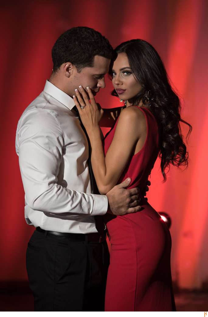 COUPLE WITH A RED DRESS AND SUIT AND WHITE LONG SHIRT