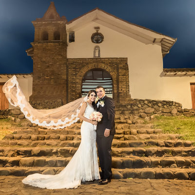 bride and groom in front of their church at night