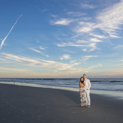 Engagement session at the beach at sunrise with blue sky
