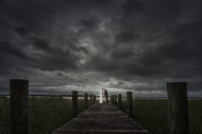 BRIDE AND GROOM ON A PIER ON THEIR WEDDING DAY