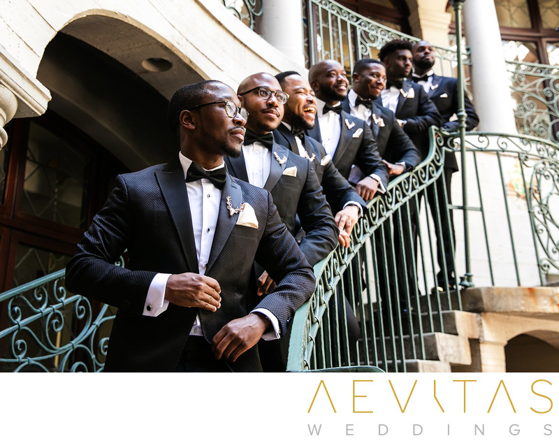 Creative groomsmen portrait on wrought iron staircase