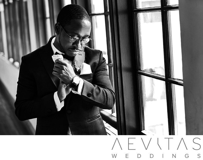 Candid shot of groom getting ready in black and white