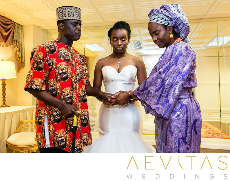 Bride and parents pray during Nigerian wedding in LA