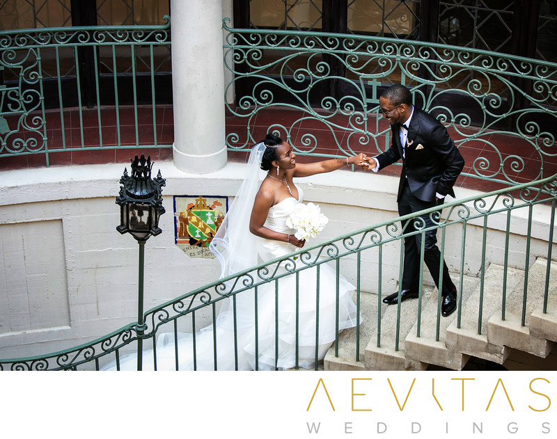 Groom leads bride up wrought iron staircase