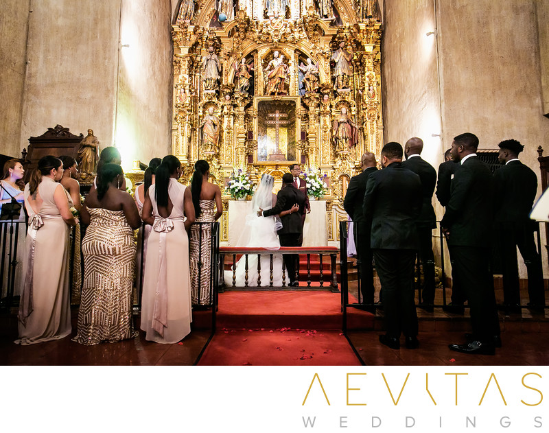 Couple and bridal party at gilded altar of Mission Inn