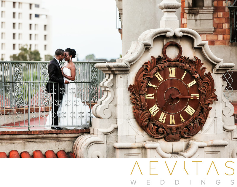 Couple portrait beside huge clock at Mission Inn